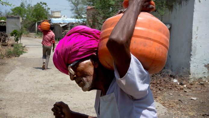 Dorpsbewoners dragen water naar hun huis.