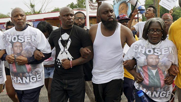 De vader van Michael Brown (tweede van rechts) leidt de herdenkingsmars, een jaar na de dood van zijn zoon.