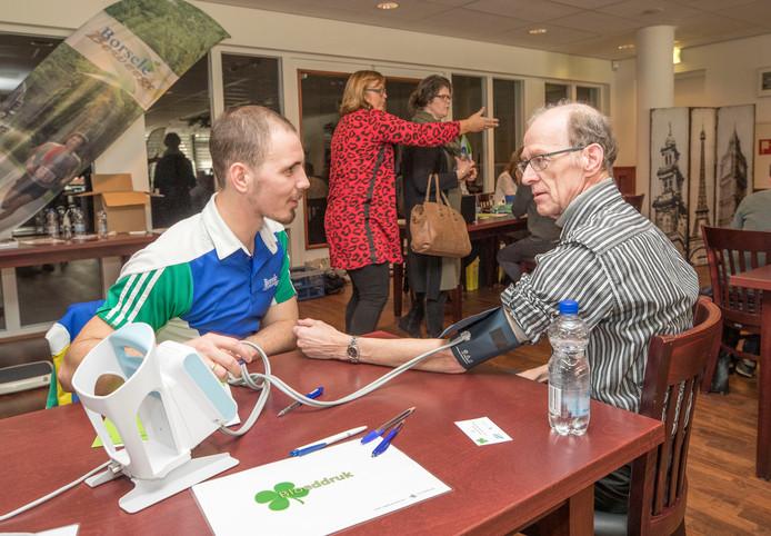 Dennis Walhout (links) van de gemeente Borsele vertelt Jan Slabbekoorn (62) dat zijn bloeddruk in orde is.