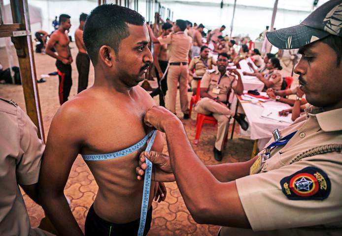 Een Indiase politie-ambtenaar meet de borstkas van een sollicitant voor de functie van politieagent in Thane, aan de rand van Mumbai. Bijna 50.000 kandidaten solliciteerden voor de 238 posten in Thane City. Foto Divyakant Solanki