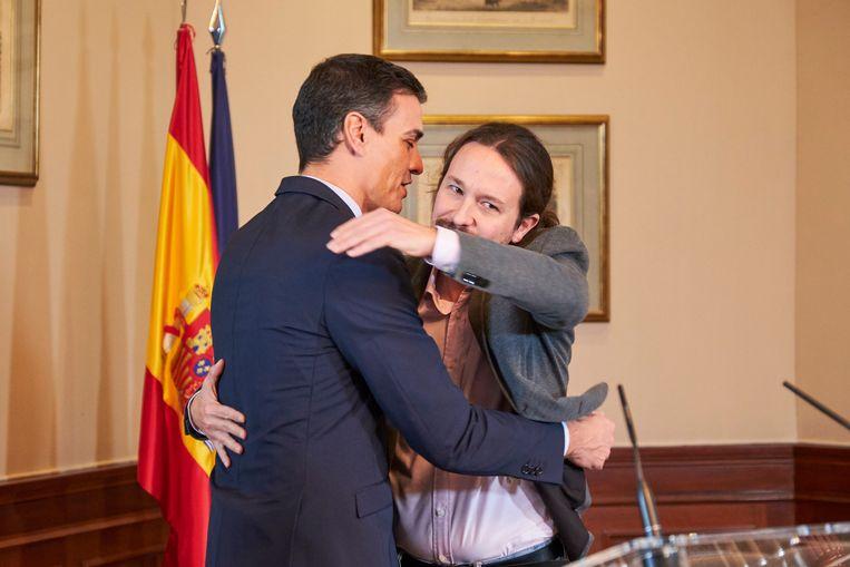 Sánchez en Iglesias bezegelden het principeakkoord met een stevige omhelzing.   Beeld Getty