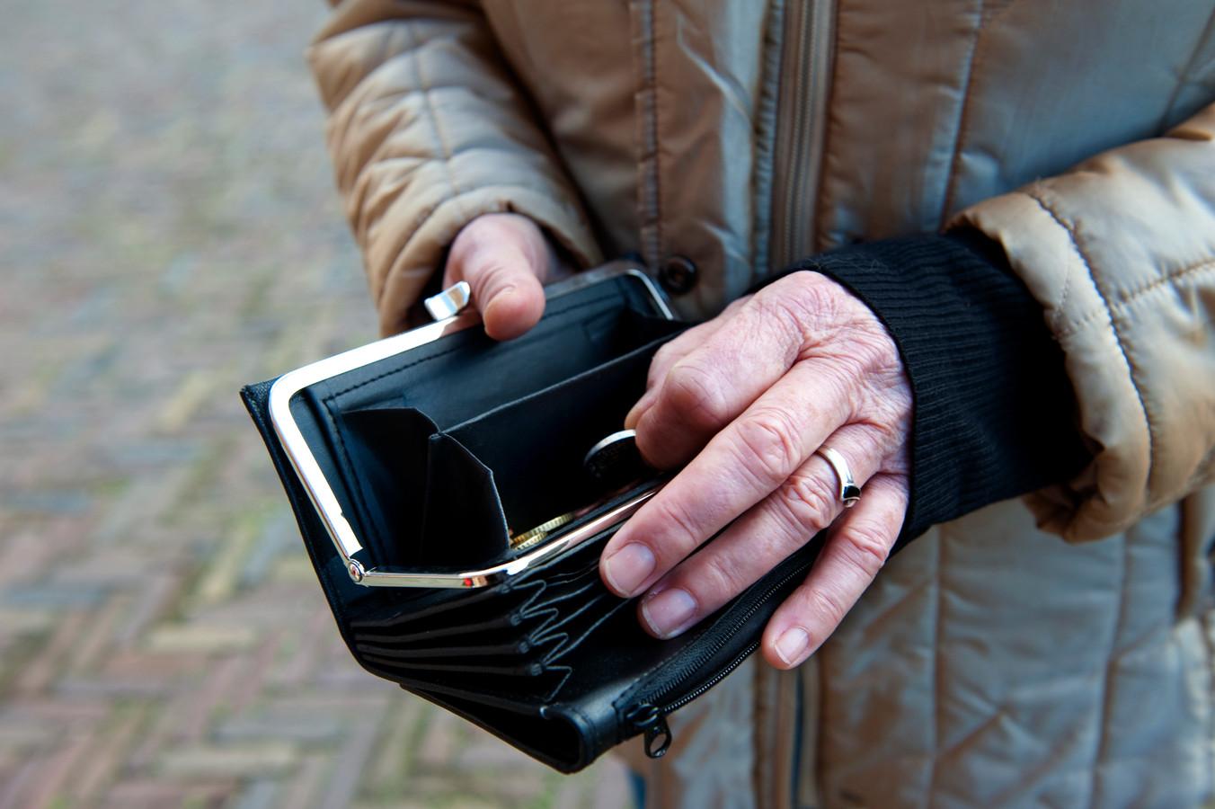 Oudere zoekt naar geld in haar portemonnee.