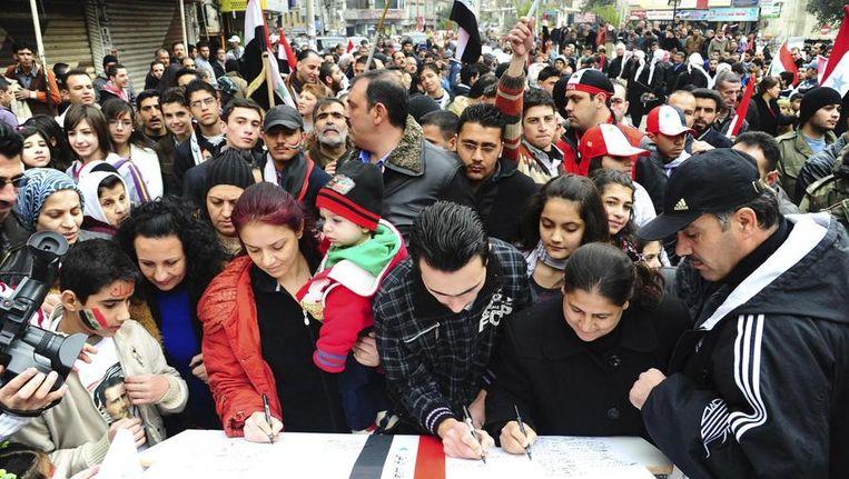 Demonstranten laten hun steun voor president Assad zien door 'de langste brief ooit' te ondertekenen, 15 januari 2011. Beeld reuters