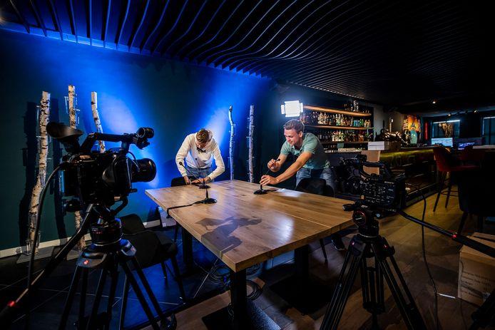 Lance Kooij (links) en Rob van Veen leggen de laatste hand aan de TV-tafel in café De Burcht in Honselersdijk. Dit is het 'zenuwcentrum' van de Honselse Feestweek, die zich voornamelijk online afspeelt.