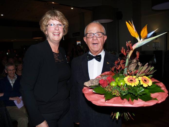 Gerrit Beunk kreeg tijdens zijn huldiging ook een bos bloemen. Links staat Karin van Berkel, voorzitter van Sempre Crescendo.