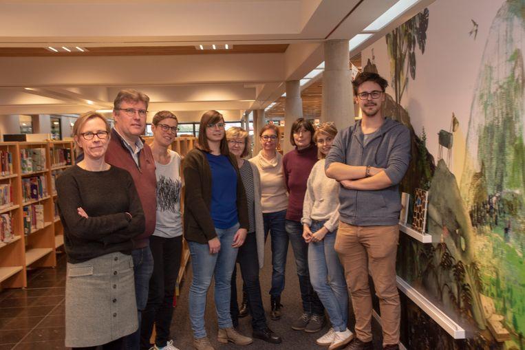 De bibliotheekmedewerkers in de vernieuwde bibliotheek van Wetteren aan één van de blikvangers : een wandschilderij van Kaatje Vermeire.
