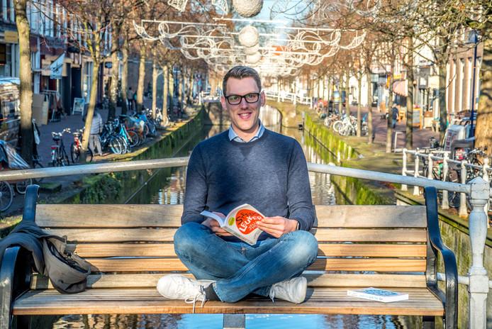 Jelle Hermus op een bankje op de Cameretten, met in zijn hand zijn eerste boek Steeds Leuker.