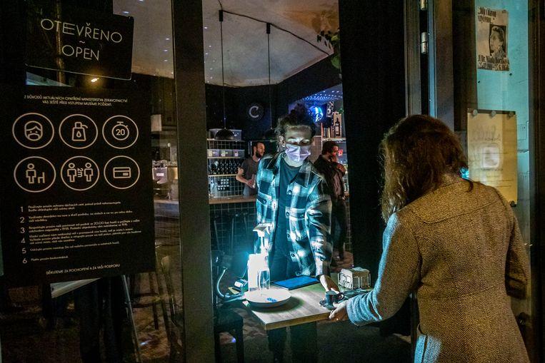 In de Tsjechische hoofdstad Praag doet een klant van een café buiten een bestelling. Sinds woensdag zijn alle horeca gesloten vanwege een oplopend aantal coronabesmettingen in het land.  Beeld Getty Images