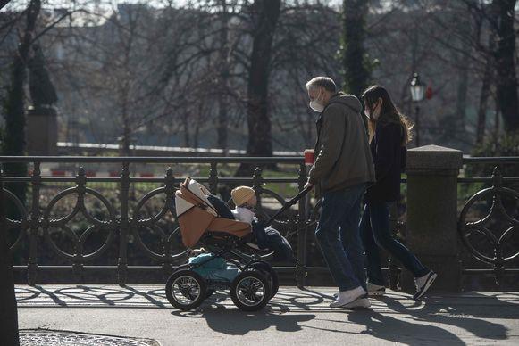 Een familie op  wandel in een park in Praag. Ook het kindje in de kinderwagen zal vanaf morgen een mondkapje moeten dragen.