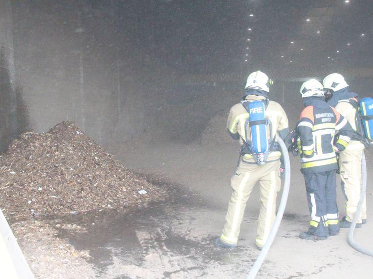 De brandweer kwam de berg afvalhout nat spuiten.