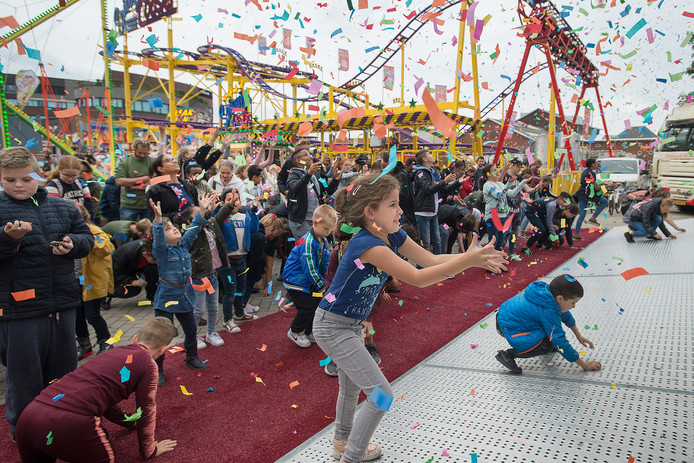 Grabbelen en graaien naar gratis kaartjes verstopt tussen de afgeschoten confetti bij de opening van de kermis in Roosendaal.
