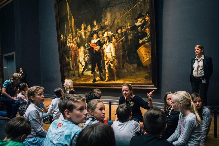 Leerlingen voor de Nachtwacht van Rembrandt in het Rijksmuseum in Amsterdam. Beeld Marcel Wogram / de Volkskrant