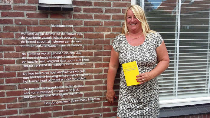 Anne-Marie Maartens bij het meestersonnet op de voorgevel van haar woning in Ellemeet
