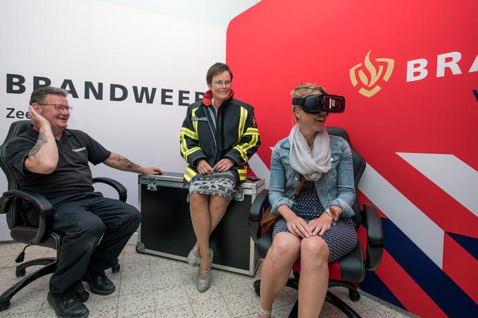 Dorina Willemse test de VR-bril in de pop-up store. In het midden burgemeester Ger van de Velde, links zit Ronald van Leeuwen van Brandveilig Leven.