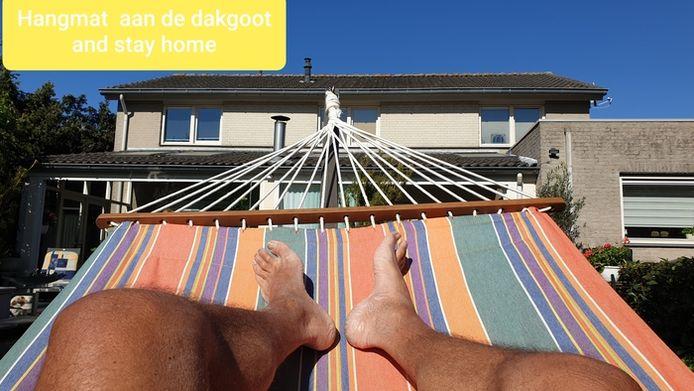 In een hangmat liggen, dat kan ook in de tuin. Deze creatieveling hing de zijne op aan de dakgoot. Gaat ook prima, zie je wel. We zien de benen van Cornelis Knetemann uit Oosterhout. Hij zou eigenlijk naar Duitsland op vakantie gaan, maar in eigen tuin valt ook genoeg te relaxen.