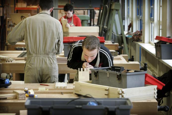 Leerlingen ROC bezig met zwaluwstaartverbinding tijdens opleiding tot meubelmaker.