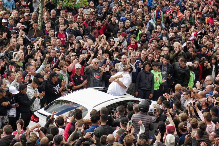 Het iconische beeld van de vader van Nouri uit het dak van een auto. Beeld Stanley Gontha