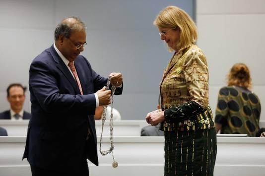 Wethouder Rabin Baldewsingh hangt Pauline Krikke de Haagse ambtsketen om.
