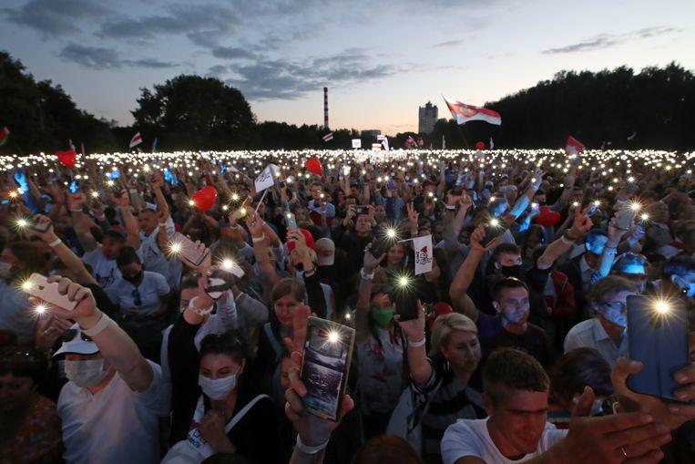 Mensen gebruiken de zaklampen op hun telefoons om te laten zien dat ze presidentskandidaat Svetlana Tichanovskaja steunen. Beeld Nataliya Fedosenko/TASS