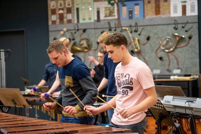 De slagwerkgroepen van muziekverenigingen Harmonie Wierden en EMOS uit Daarle geven een concert als voorbereiding van een concours.