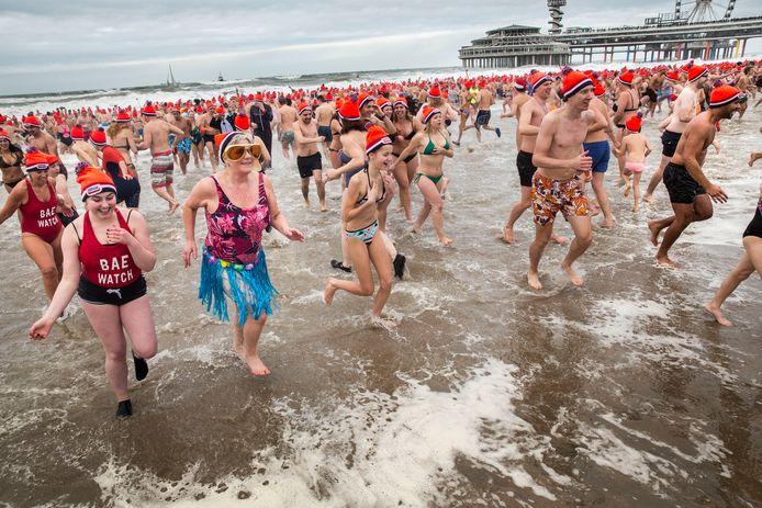 Deelnemers aan de traditionele Unox Nieuwjaarsduik rennen de Noordzee in voor een verfrissende duik. Ter illustratie.