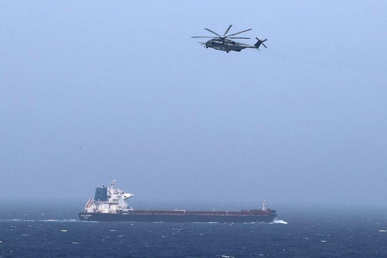 Een Amerikaanse legerhelikopter en een olietanker in de Perzische golf.  Beeld REUTERS