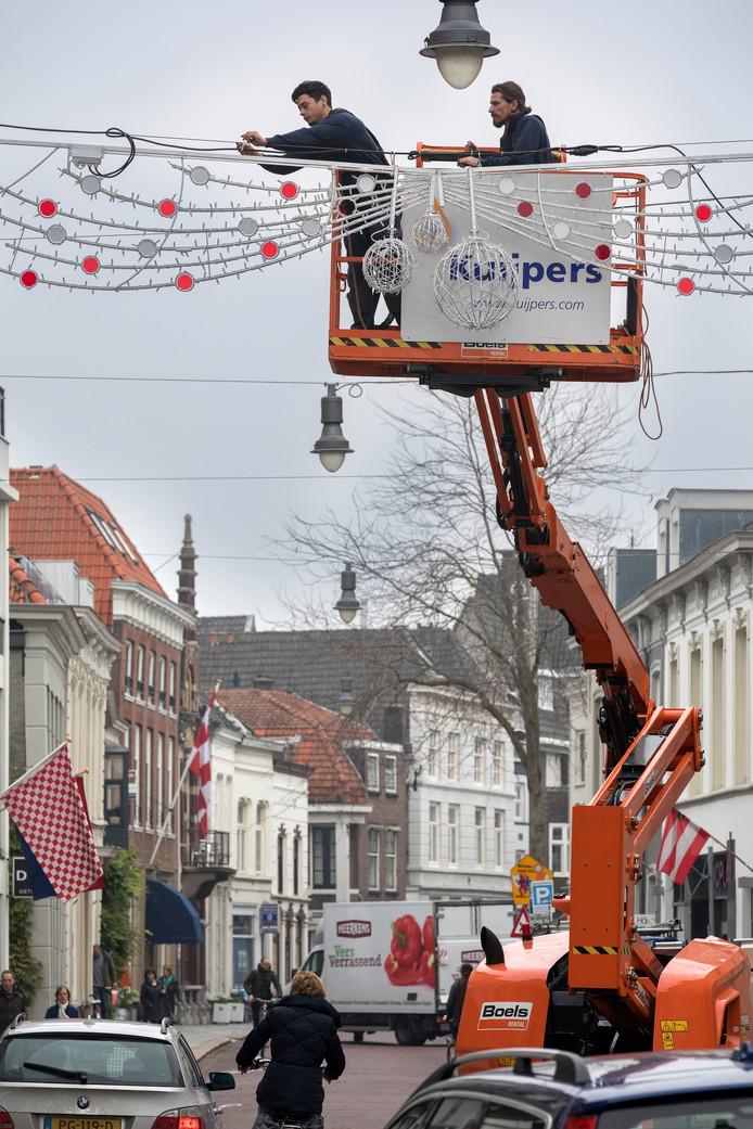 Kerstverlichting wordt opgehangen in de Vughterstraat