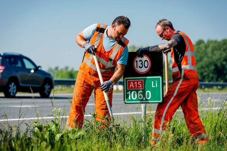 Een medewerker van Rijkswaterstaat plaatst een hectometerbordje met snelheidsaanduiding langs de A15 bij Herwijnen.  Beeld ANP