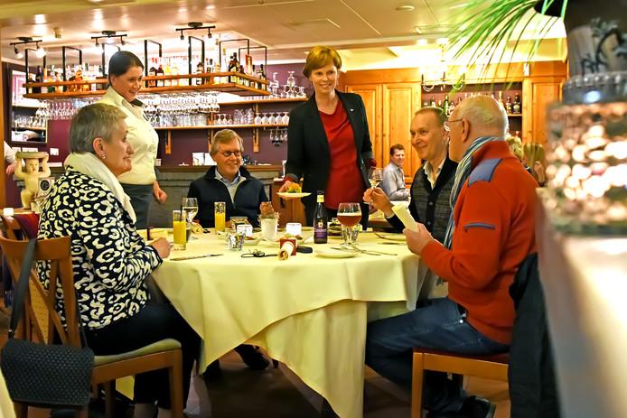 Gastvrouw Rachelle (l) en eigenaresse Marianne (r) aan tafel bij hun gasten.