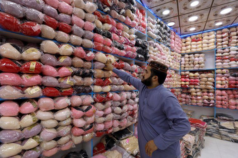 Een winkelier in Peshawar haalt uit China geïmporteerd vrouwenondergoed uit de schappen. Beeld REUTERS