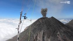 Paraglider vliegt over rokende vulkaan Fuego