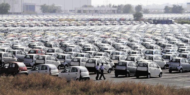 Beveiligers bewaken rijen en rijen Nano?s op het terrein van de Tata autofabriek in Sanand, India. (FOTO AP) Beeld AP