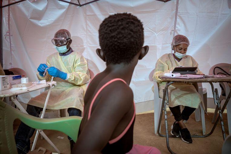 Een jong meisje wacht op de dokter die haar vaccinatie voorbereidt, op de plek waar Vianney Kambale met zijn kinderen een ebola-vaccinatie kwam halen. Beeld Sven Torfinn