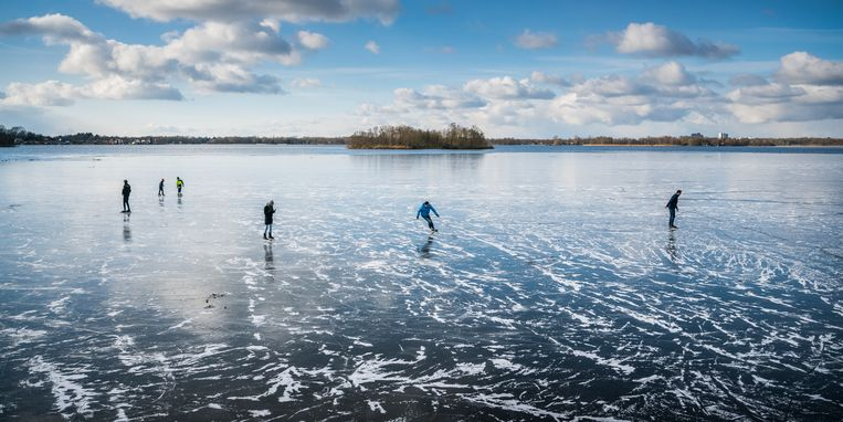 Schaatsers op het nog zingende en krakende ijs van het Paterswoldsemeer. Beeld © Kees van de Veen