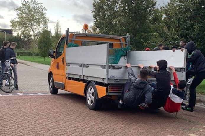 Jongeren hangend aan een busje van de gemeentewerkers.