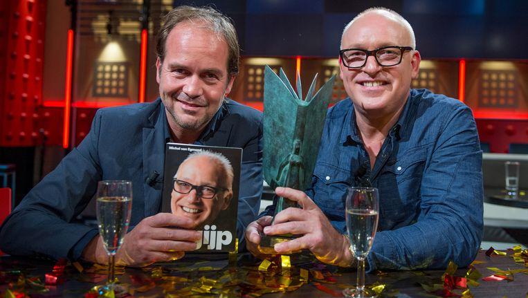 Schrijver Michel van Egmond (L) en René van der Gijp met het boek 'Gijp' tijdens de bekendmaking van de NS Publieksprijs 2013 in de uitzending van De Wereld Draait Door. Beeld anp