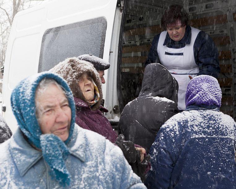 Inwoners van Kupuvate bij de bus met levensmiddelen. Beeld Esther Hessing