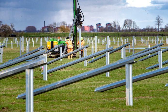 De geraamtes van de duizenden zonnepanelen staan en liggen klaar in het weiland in Wilp en worden met een heimachine in de grond geslagen.