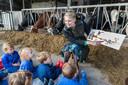 Marianne van der Sloot leest voor in de stal met koeien bij kinderdagverblijf Het Vrolijke Koetje.