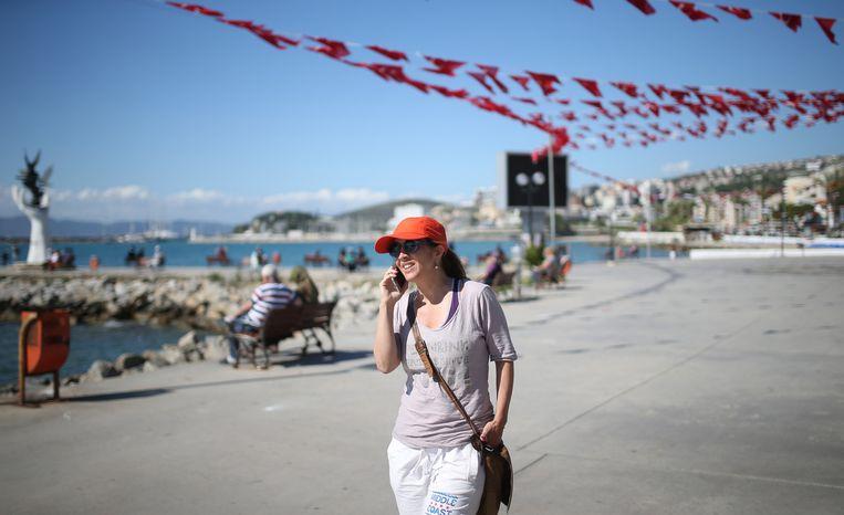 Umar voert een telefoongesprek op de boulevard langs het strand, de dag na haar vrijlating. Beeld anp