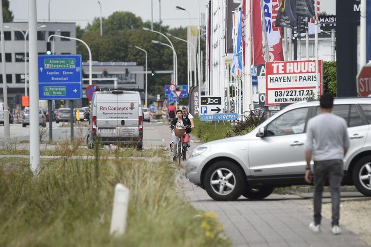 De vele op -en afritten van de winkels maken fietsen op de Bredabaan levensgevaarlijk.