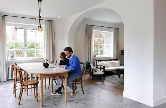 De oorspronkelijke boog in de leefruimte werd behouden en de nieuwe ramen kregen een klassieke vakjesindeling. De Thonet-stoelen zijn maar liefst 150 jaar oud.