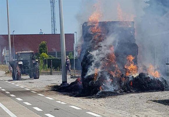 De hooiwagen staat nog fel in brand. Op de achtergrond is te zien hoe de banden van de tractor eveneens vuur vatten.