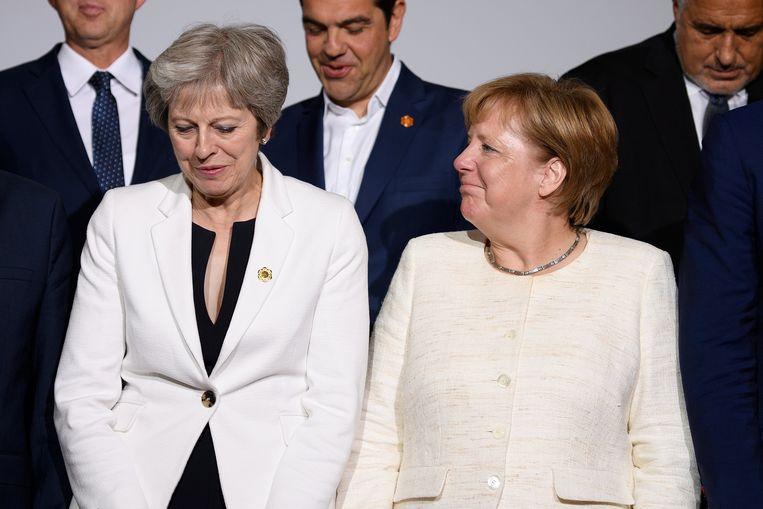 Theresa May en Angela Merkel ontmoetten elkaar gisteren tijdens een conferentie in Londen. Beeld REUTERS