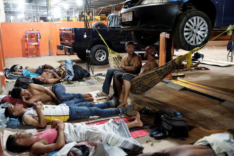 Venezolanen rusten uit in een garage bij het busstation van Boa Vista. Beeld REUTERS
