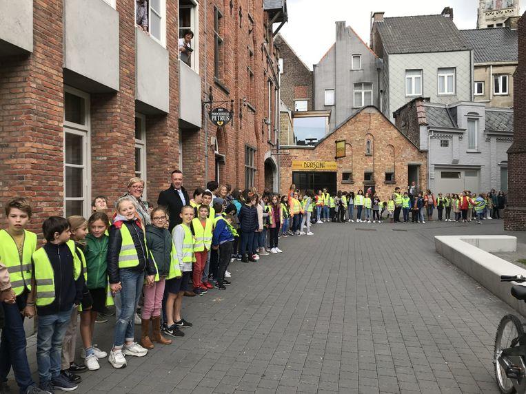 De leerlingen vormden een grote kring rond de Sint-Michielskerk.
