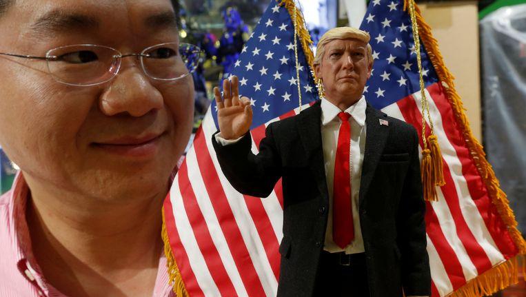 De directeur van de Chinese poppenfabrikant DID poseert met een pop van president Trump. Beeld REUTERS