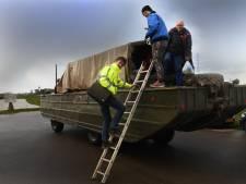 Deze mannen gaan per amfibievoertuig naar hun werk aan de Waal bij Echteld