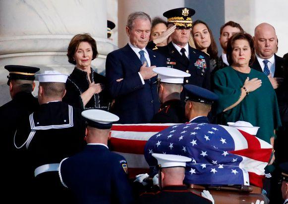 De voormalige president Bush en zijn familie kijken toe hoe het lichaam van de pater familias Bush wordt binnengebracht in het Capitool.