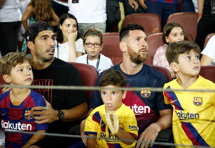 Luis Suárez (links) en Lionel Messi met hun zoontjes op de tribune bij Barça - Real Betis.